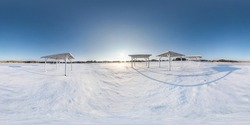 Winter full spherical seamless panorama 360 degrees angle view snow covered deserted beach with gazebos near lake  in snowy park with blue sky at evening in equirectangular projection. VR AR content