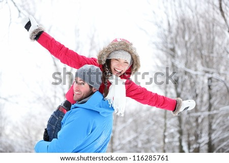 Winter fun couple playful together during winter holidays vacation outside in snow forest. Happy young interracial couple, Asian woman, Caucasian man.