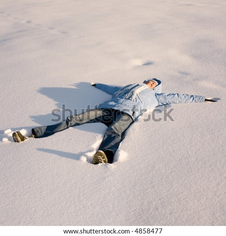 Winter fun - Happy young girl  lying in the snow after skiing
