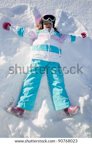 Winter fun - Snow Angel - little girl playing in snow