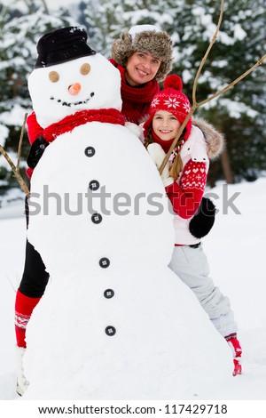 Winter fun, snowman -  family enjoying winter - stock photo
