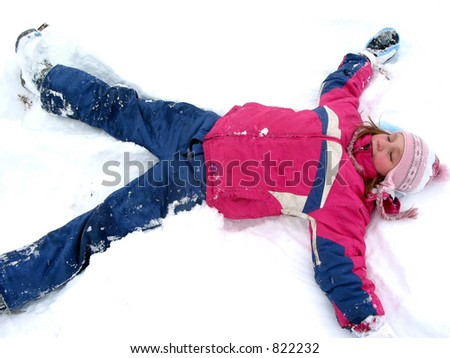 Winter fun: young girl making a snow angel on fresh white snow