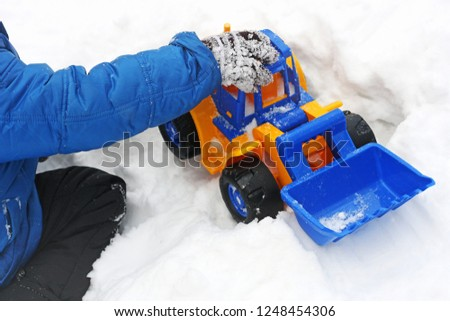 Winter games Baby playing in the snow. Image of a child sitting on white snow and playing with a toy excavator.