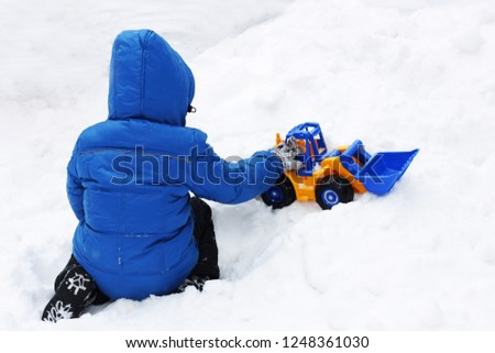 Winter games. Child playing in the snow. Image of a child sitting on white snow and playing with a toy excavator.Rear view.