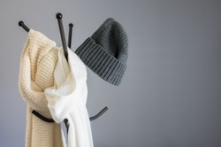 Winter garment accessories, minimal style of white cotton scarf, soft knitted scarf, and casual knitted hat hanging on a coat stand against the wall
