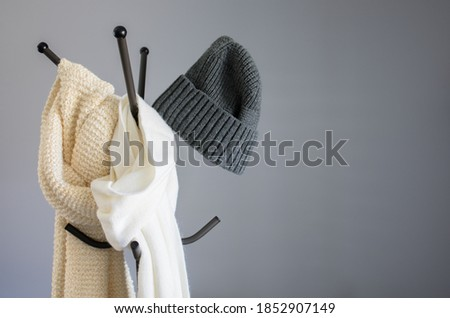 Winter garment accessories, minimal style of white cotton scarf, soft knitted scarf, and casual knitted hat hanging on a coat stand against the wall Foto d'archivio ©