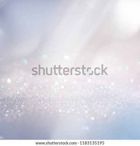 Winter gentle sparkle snowy blurry background in light blue pink tones. Christmas backdrop defocused with beautiful light, abstract shiny snowflakes flake of snow in blur, copy space