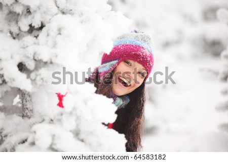 winter girl behind snow tree