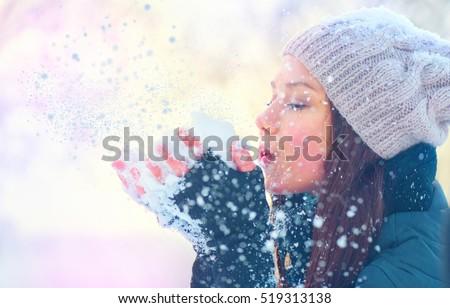 Winter girl blowing snow. Beauty Joyful Teenage Model Girl having fun in winter park. Beautiful young woman laughing outdoors. Enjoying nature.