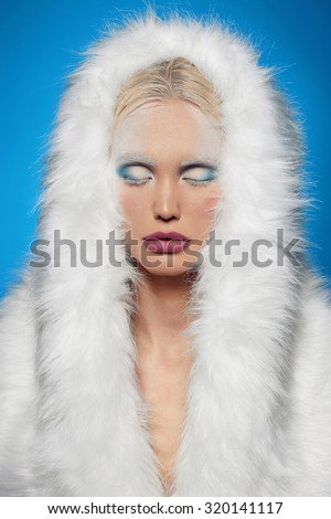 Stock Photo winter girl in fur.halloween snow queen.beautiful blond young woman.iced make-up