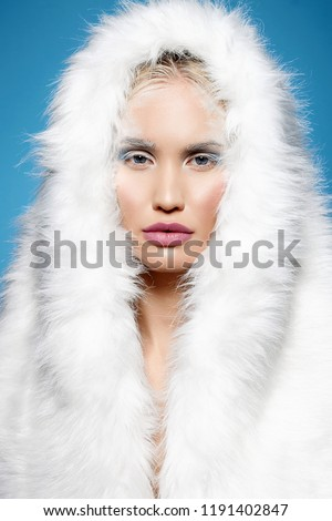 Stock Photo winter girl in fur hood. halloween snow queen make-up. beautiful blond young woman