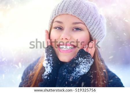 Winter girl portrait. Beauty Joyful Teenage Model Girl touching her face skin and laughing, having fun in winter park. Beautiful young woman laughing outdoors. Enjoying nature.