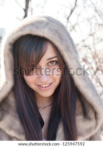 Winter girl portrait in a fur coat with bokeh background.