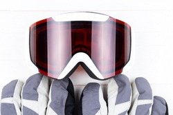 Winter gloves and goggles on white natural wooden table background. Concept of skiing or snowboarding. Flat lay top view.