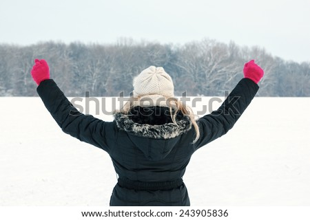 winter happy woman in snow holding snow ball in hand for snowballing with thumb up outside on sunny cold winter vintage day.Portrait of smiling female model with pink gloves and hat with scarf in snow