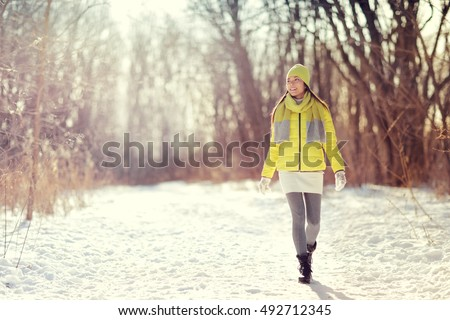 Winter happy woman walking in snow outdoors nature. Joyful young person relaxing on an outdoor walk activity in snowy forest landscape wearing warm yellow fashion outerwear jacket boots, scarf, hat. - Shutterstock ID 492712345
