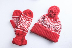 Winter hat and mittens knitted with jackard on white background. Top view. Flst lay. Christmas background