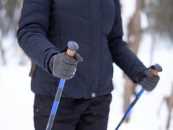 Winter hiking, details. Human hands with handles of nordic walking sticks, close up, selective focus. Outdoor pursuits, sport, fitness, activity, healthy lifestyle concept