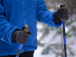 Winter hiking, details. Human hands with handles of nordic walking sticks. Person in blue sweatshirt make movement, close up, selective focus. Outdoor pursuits, urban fitness, activity, healthy