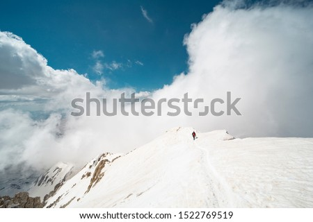 Winter hiking in the mountains with a backpack crampons and ice axes #1522769519