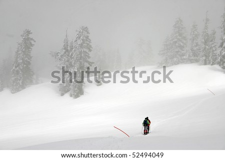 Winter hiking view while hikers cross snow field.