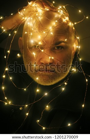 Winter holiday and xmas. Christmas man with beard on face and garland. Garland on santa claus man as decoration. New year guy with illuminated wire. Party and celebration. #1201270009