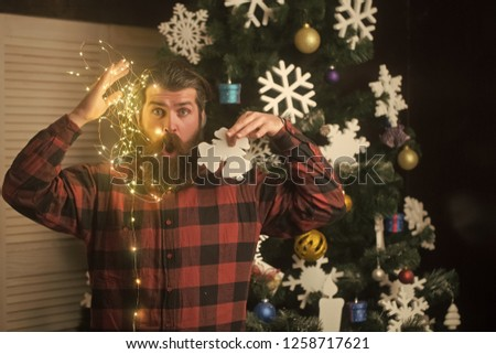 Winter holiday and xmas. Christmas man with beard on face and garland. Garland on santa claus man as decoration. New year guy with illuminated wire and toy at christmas tree. Party and celebration. #1258717621