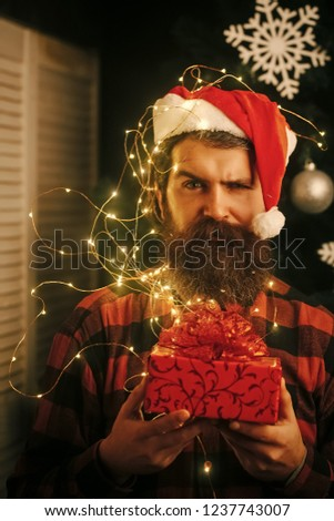Winter holiday and xmas. Christmas man with beard on serious face, garland. Garland on santa claus man at decoration. New year guy with illuminated wire , present box and toy. Party and celebration. #1237743007