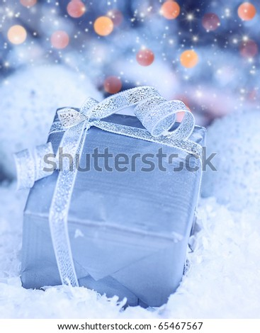 Winter holiday background with blue present gift box, silver ribbon ornament & Christmas snow decoration
