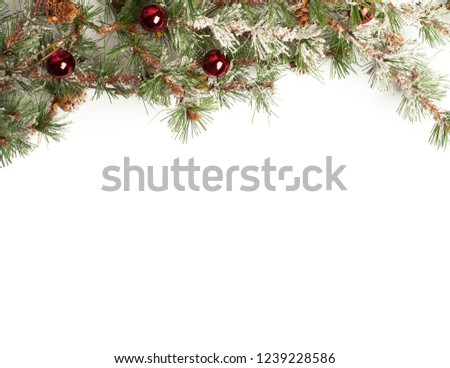 Winter holiday background with fir leaf border. Isolated Christmas Frame with tree branches. Christmas motifs. branches of a Christmas tree with ornaments on the white background #1239228586