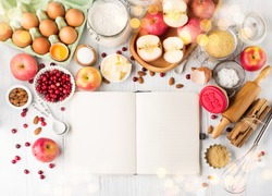 Winter holiday baking concept. Cooking baking background with empty cookbook, ingredients, spices and utensils. Baking traditional winter pie. Rustic white wooden table, top view, copy space.