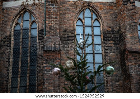 Winter holiday in Europe. Christmas tree decorated with silver and golden Christmas ornaments against blurry background of Gothic style arch windows on old weathered brick walls of medieval building. #1524952529