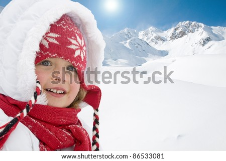 Winter holiday - portrait of cute girl, snowy mountains in background (space for text)