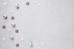 Winter holiday vibes. Border made of festive decorations, baubles and snowflakes on grey background. Seasonal background, Christmas, New Year composition. Flat lay, copy space