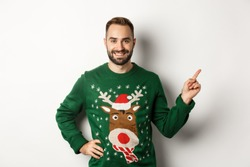 Winter holidays and christmas. Handsome bearded adult man pointing finger right at promo banner, standing in funny sweater against white background