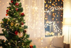 winter holidays and interior concept - close up of decorated christmas tree, sofa and garland on window at home in evening