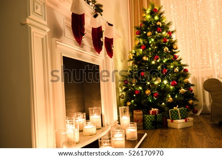 Winter holidays atmosphere in a warm room with a christmas tree full of lights and toys near a cute fireplace with candles and present toys. Christmas interior. New year design.
