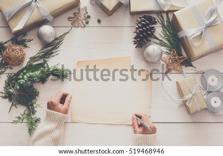 Winter holidays background. Gift wrapping and decorating christmas present, boxes in craft paper with satin silver ribbon. Top view of hands on white wood table sign greeting card, copy space