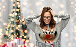winter holidays, celebration and people concept - happy young woman wearing ugly sweater with reindeer pattern over festive christmas tree lights background