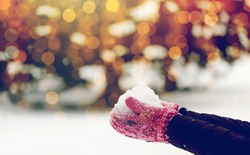 winter holidays, christmas and people concept - close up of woman holding snow outdoors