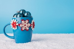 Winter holidays concept. Close up photo of blue decorated coffee cup full of small baubles standing in fluffy white snow on blue background with copyspace