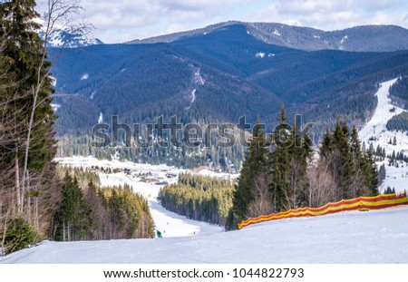 Winter holidays in the mountains. Mountain-skiing slope on the slopes of the Carpathian Mountains #1044822793