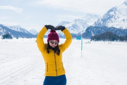 Winter holidays in the snow - lifestyle portrait of young happy and beautiful Asian Chinese girl doing love symbol with arms enjoying playful at frozen lake