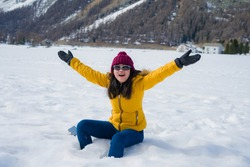 Winter holidays in the snow - lifestyle portrait of young happy and beautiful Asian Japanese girl enjoying playful at frozen lake in snowy mountains at Swiss Alps