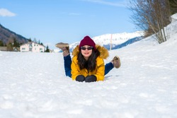 Winter holidays in the snow - lifestyle portrait of young happy and beautiful Asian Korean girl enjoying playful at frozen lake in snowy mountains at Swiss Alps