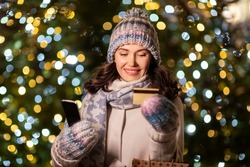 winter holidays, season sale and people concept - happy smiling young woman with christmas gifts in shopping bags, credit card and smartphone over festive lights