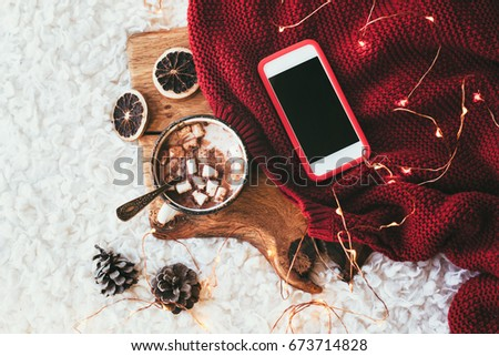 Winter homely scene. Warm knit blanket, phone with blank screen and cup of sweet cocoa with marshmallows on wooden tray in bed. Lazy cold weekend.