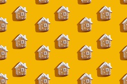Winter house pattern. Orange seamless background. Christmas celebration creative ornament. Beige gingerbread home design with white snow decor minimalist symmetrical composition isolated on bright