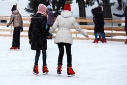 Winter ice rink. The girls in the red skate riding on the ice. Active family sport during the children Christmas winter holidays. School sports clubs. Dnipro city, Dnepropetrovsk, Ukraine