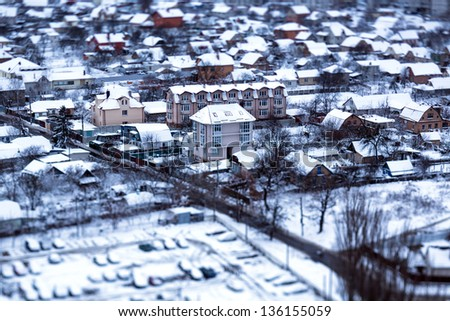 Winter in a village, houses with snowy roofs, tilt-shift - stock photo